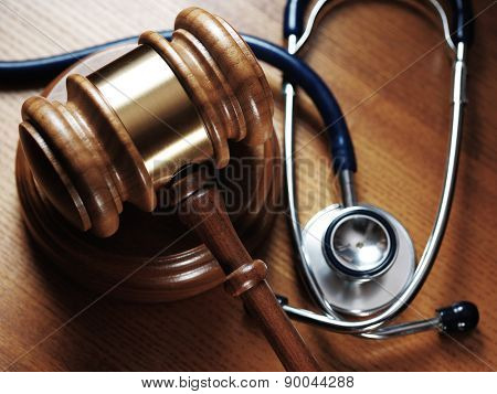 Judge gavel and stetaskop on wooden background. Close up