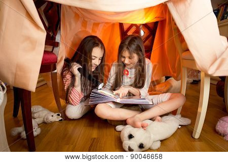 Girls Reading Book With Flashlight At House Made Of Blankets