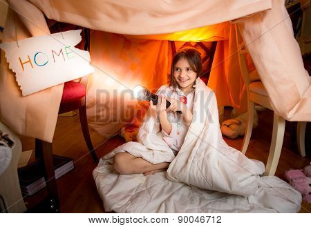 Cute Smiling Girl Playing With Flashlight In House Made Of Blankets