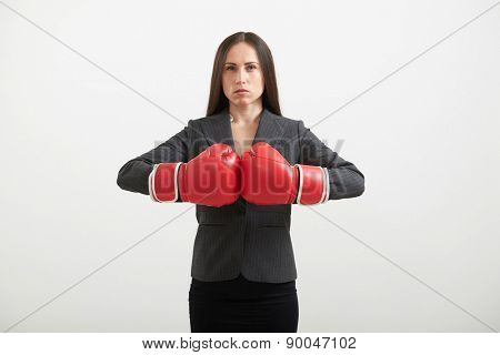 Confident businesswoman in red boxing gloves looking at camera and ready for fight over light grey background