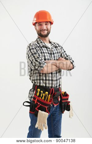 confident smiley workman with tools in orange helmet standing over light background