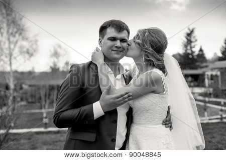 Black And White Portrait Of Bride Giving A Kiss On Grooms Cheek