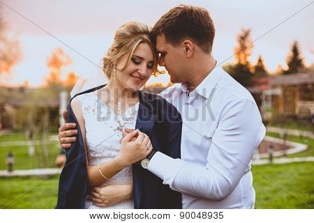 Toned Portrait Of Careful Groom Embracing Bride In Park At Sunset