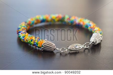 Knitted Bracelet From Small Multi-colored Beads Close Up