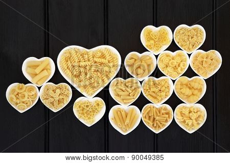 Pasta food selection in heart shaped porcelain dishes over dark wooden background.