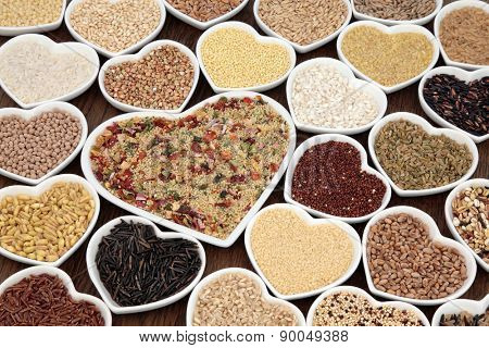 Large cereal and grain food selection in heart shaped porcelain bowls. Vegetable couscous in large dish.