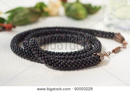 Knitted Necklace From Dark Beads On A Textile Background
