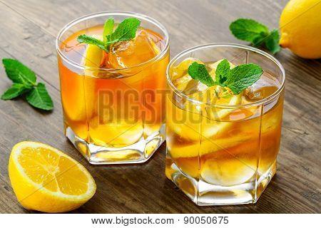lemon ice tea on brown wooden table with lemons around
