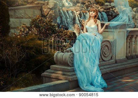 Young Girl Near A Waterfall In The Garden.