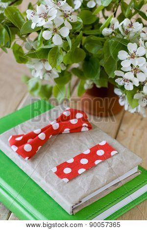 A Bouquet Of Flowering Branches Of Fruit Trees And An Old Notepad On Unpainted Wooden Background