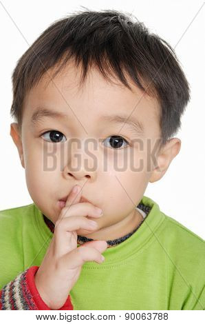 A little boy keeping silence by covering his mouth by hands