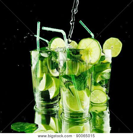 Pouring fresh mojito cocktail in glasses isolated on black background