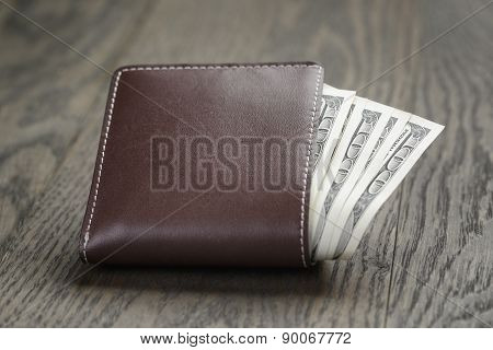 leather wallet on wood table with dollar bills