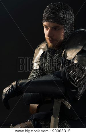 Ancient knight in metal armor with sword