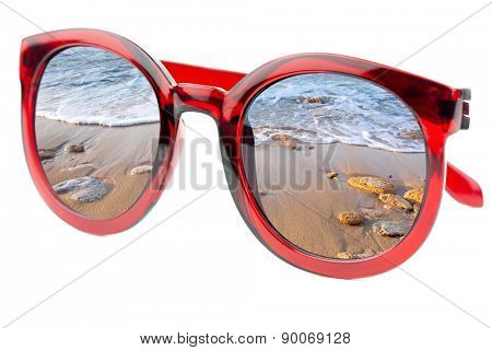 Summertime concept -  Sunglasses have a beach with wave of sea  reflecting on isolated white background