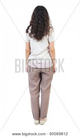 back view of standing young beautiful  woman.  girl  watching. Rear view people collection.  backside view of person.  Isolated over white background. curly girl standing with her hands down