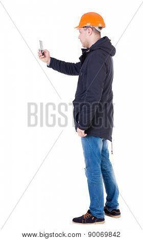 Backview of an engineer in construction helmet stands and using a mobile phone. Standing young guy.  Isolated over white background. Foreman photographs on the phone what he sees.