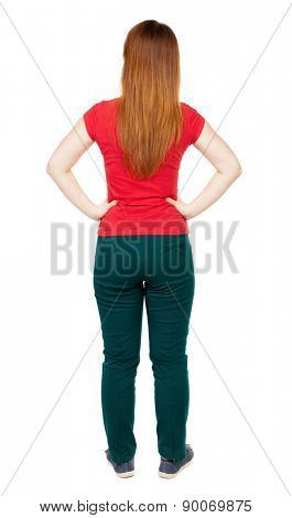 back view of standing young beautiful  woman in jeans. girl watching. Rear view people collection. backside view person. Isolated over white background. girl in green pants standing with hands on hips