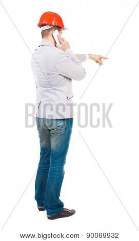 Backview of business man in construction helmet stands and enjoys tablet or using a mobile phone. Rear view people collection.  backside view of person.  young businessman gives instructions on phone