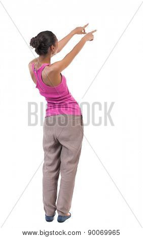 back view of woman. Young woman in vest presses down on something. Isolated over white background. Rear view people collection. . African-American woman shows her hands in the right