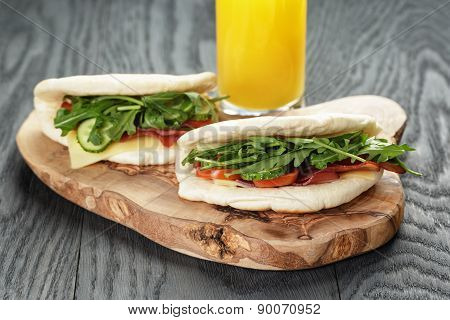 rustic sandwiches with ham arugula and tomatoes in pita bread and glass of juice, on wood table