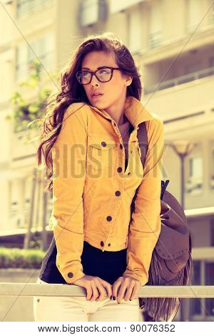 young urban woman with eyeglasses portrait,  outdoor shot in the city, retro colors