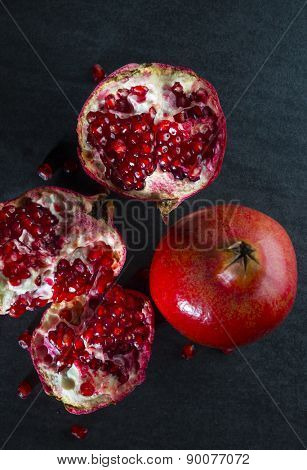 Cut pomegranate on black background with a whole fruit.