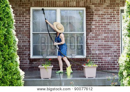 Housewife Washing The Windows Of Her House