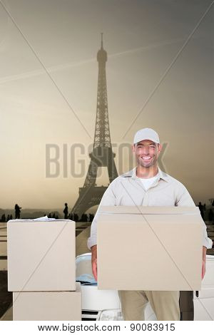Courier man carrying cardboard box against eiffel tower