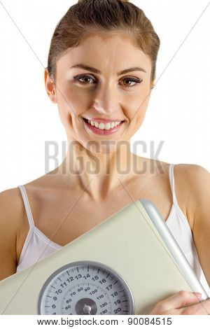 Slim woman holding weighing scales on white background