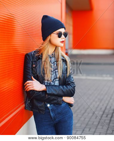 Street Fashion Concept - Stylish Woman In Rock Black Style Posing Against A Red Urban Wall