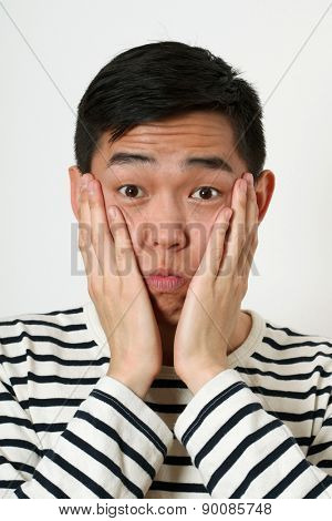 Astonished young Asian man covering his face with palms.