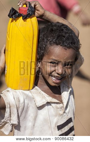 OROMIA, ETHIOPIA-APRIL 21, 2015: Unidentified boy carries water from a source to him home in Ethiopia