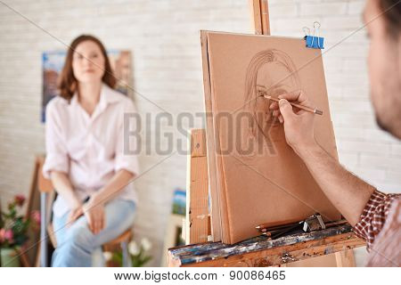 Hand of male artist drawing his muse