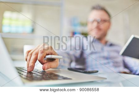 Male hand with cellphone over laptop keypad