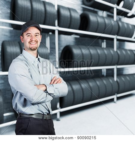 smiling garage man and tires background
