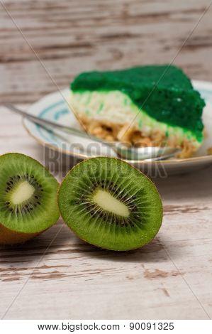 Kiwi Fruit Cut In Half In Front Of Green Slice Of Cake
