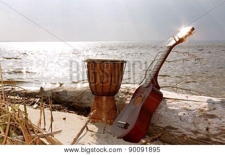 Ukulele & ethnic drum on a beach.