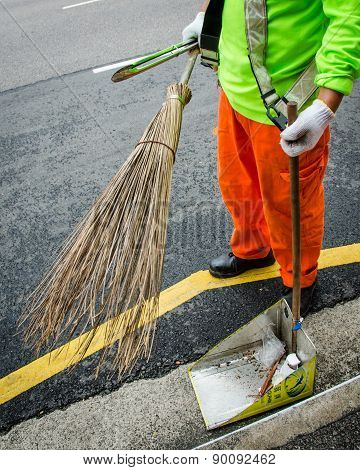 Street sweeper in Singapore uses traditional broom and makeshift pan