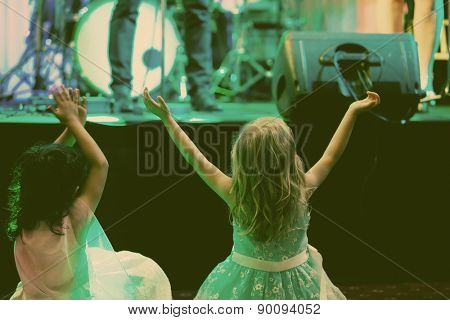 Two little girls in front of stage during rock concert vintage photo