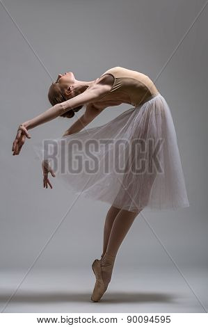 Graceful ballerina standing on toes bending the back