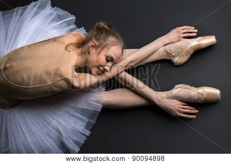 Graceful ballerina sitting on the floor