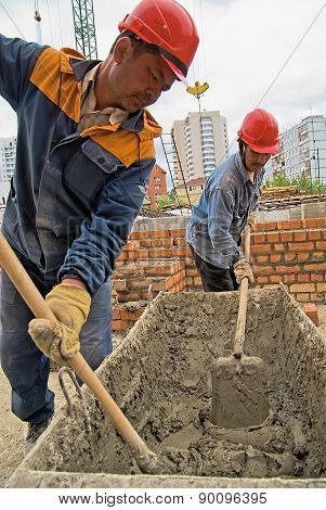 Workers knead solution for bricklayers