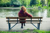 image of ponds  - A young woman is sitting and relaxing on a bench in the park by a pond - JPG
