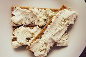 picture of crisps  - Crisp bread with cream cheese on white dish top view selective focus