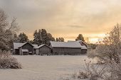 foto of farm-house  - Winter sunset scene with a tight group of old farm houses during winter - JPG