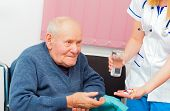 stock photo of nurse  - Nursing home assistant giving daily treatment to patient with Alzheimer - JPG