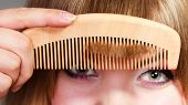 Постер, плакат: Closeup Woman Combing Her Fringe With Comb