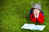 stock photo of 7-year-old  - Cute 7 years old boy lying on a grass with a book - JPG