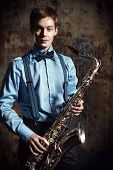 pic of saxophones  - Portrait of a musician with his saxophone - JPG